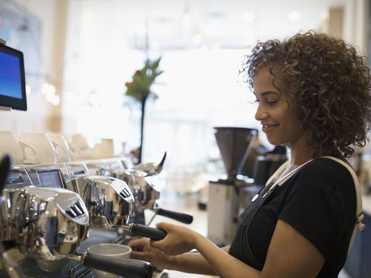 Young Woman With Curly Hair in Apron Prepares Coffee as a Barista