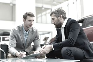 Person signing a leasing contract for a new car