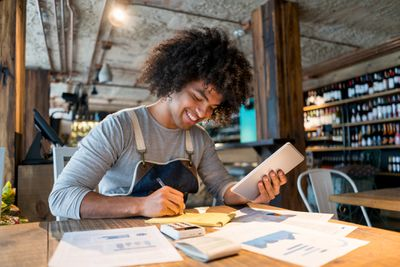 Business owner smiling and bookkeeping at a restaurant