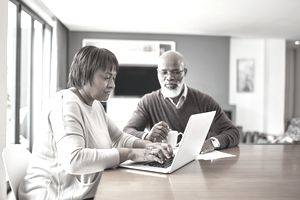 Cropped shot of a senior couple sitting together and using a laptop to work on their financial statements