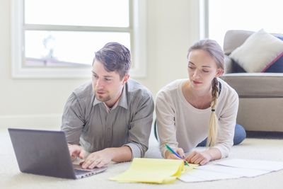 Couple doing financial planning at home on floor with laptop and papers