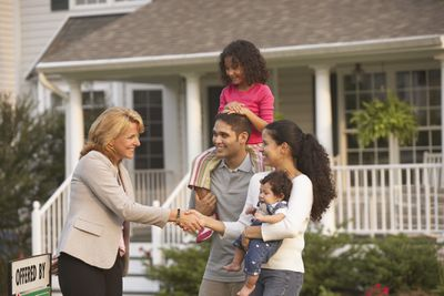 Young couple holding their children and shaking hands with a realtor in front of their new house