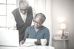 Senior couple looking over paperwork at their computer