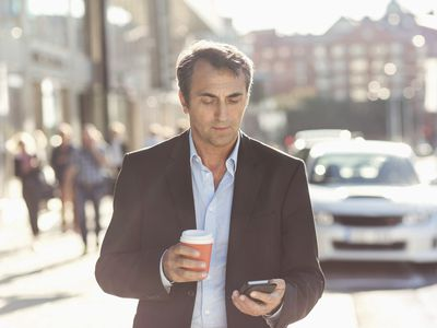Businessman using mobile phone and holding disposable coffee cup while walking on city street