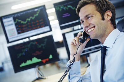 Young commodity broker talking on the phone in front of screens showing analysis information..