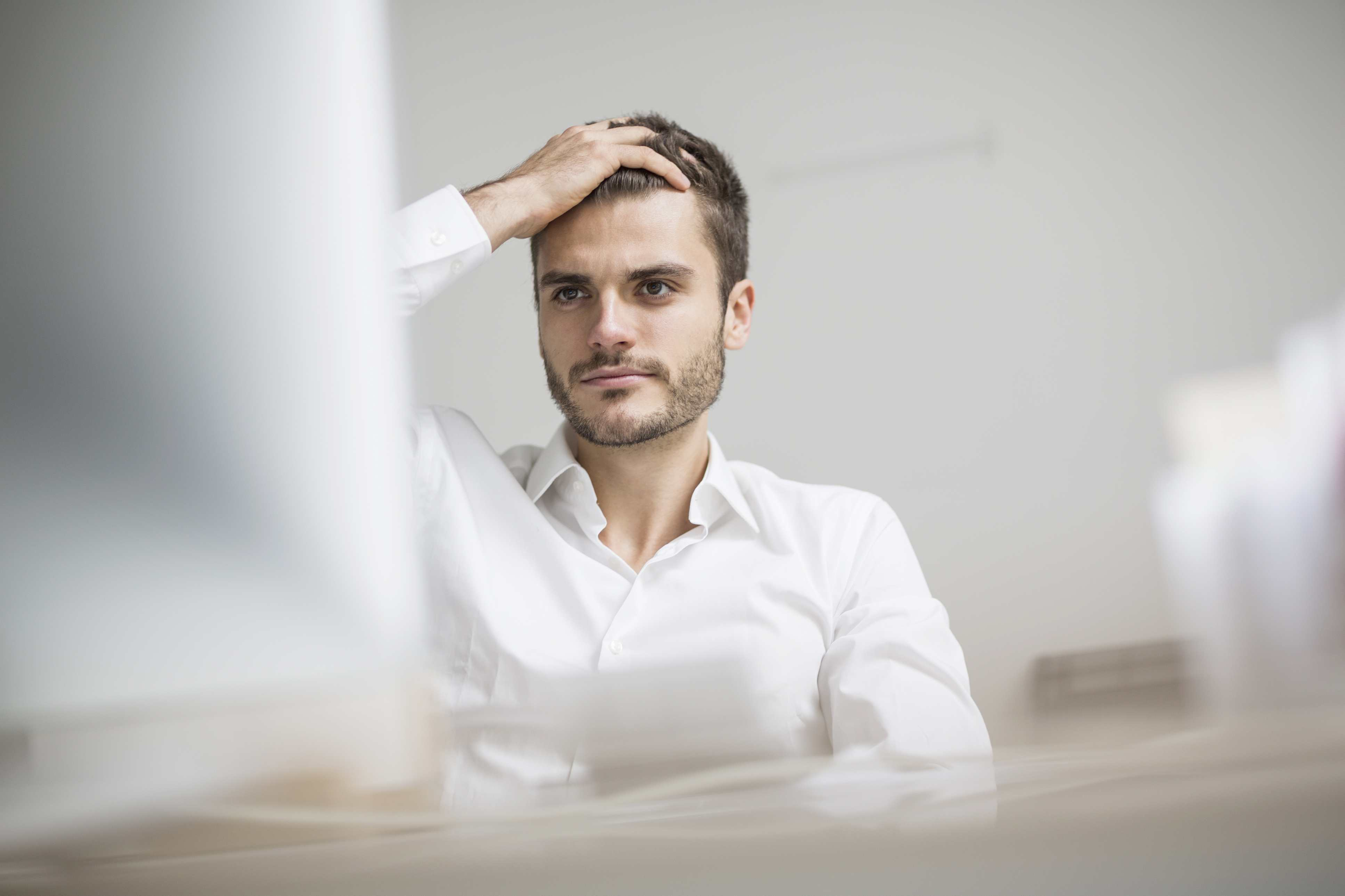 A man sits, stressed, at his computer