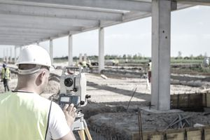Civil engineer, geodesist is working with total station on a building site