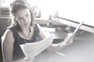 A businesswoman sits at her desk reading through paperwork