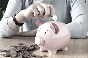 An elderly person's hand dropping pennies into a pink piggy bank