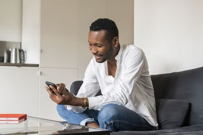Man sits on his couch, using his phone