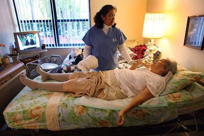 nurse looking after bed-ridden woman