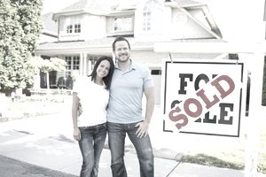A Caucasian husband and wife are posing outdoors in front of a new house.