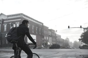 Young man riding a bike with a backpack on down a small-town main street.