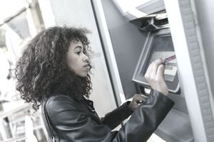 A woman uses an ATM outside of a Commerce Bank branch.
