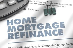 Home Mortgage Refinance application laying under a calculator