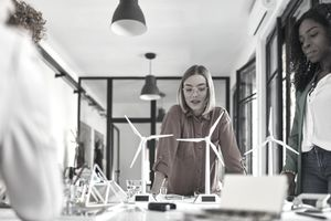 Several architects review a model of a field of wind turbines on a table in their office