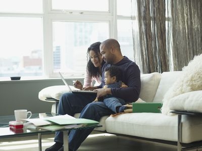 Parents with young child sitting on a sofa looking at laptop