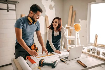 Man and woman standing over a desk with home improvement project tools and materials around them.