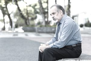 Man in tie sits on outdoor bench looking dejected