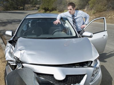 Businessman leaning against open car door looking forward at front-end damage
