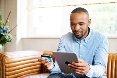A person sits on a couch holding a tablet and a credit card