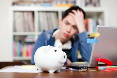 a worried college student thinking about his student loan as he looks at a piggy bank near his laptop