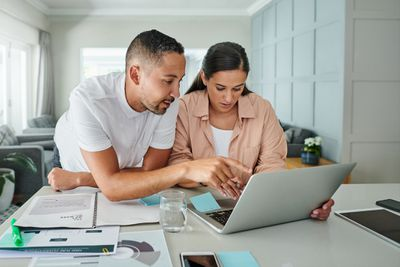 Young couple looking at laptop and paperwork at kitchen counter