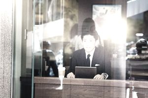 Worried Japanese job hunter at cafe looks up from tablet disappointed. Photographed in Shinjuku, Tokyo, Japan through window. Relfection of the sun and surrounding city on the glass.