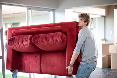 Young man moving a loveseat into a new home with packing boxes sitting in the background
