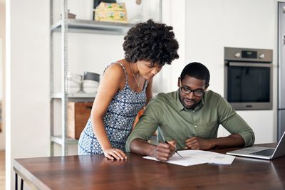 A couple goes over paperwork in their home.
