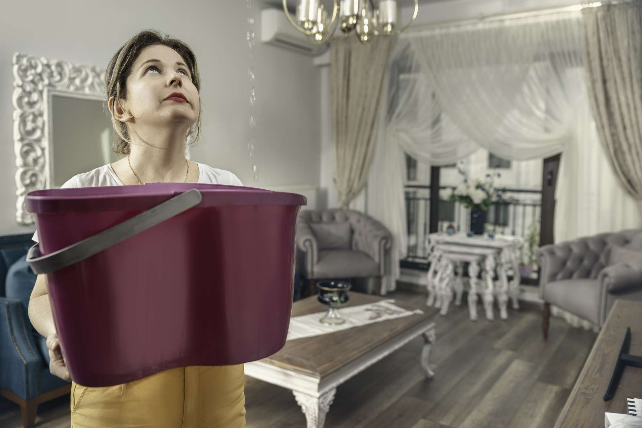 Woman catching rain from a leaky roof in a bucket