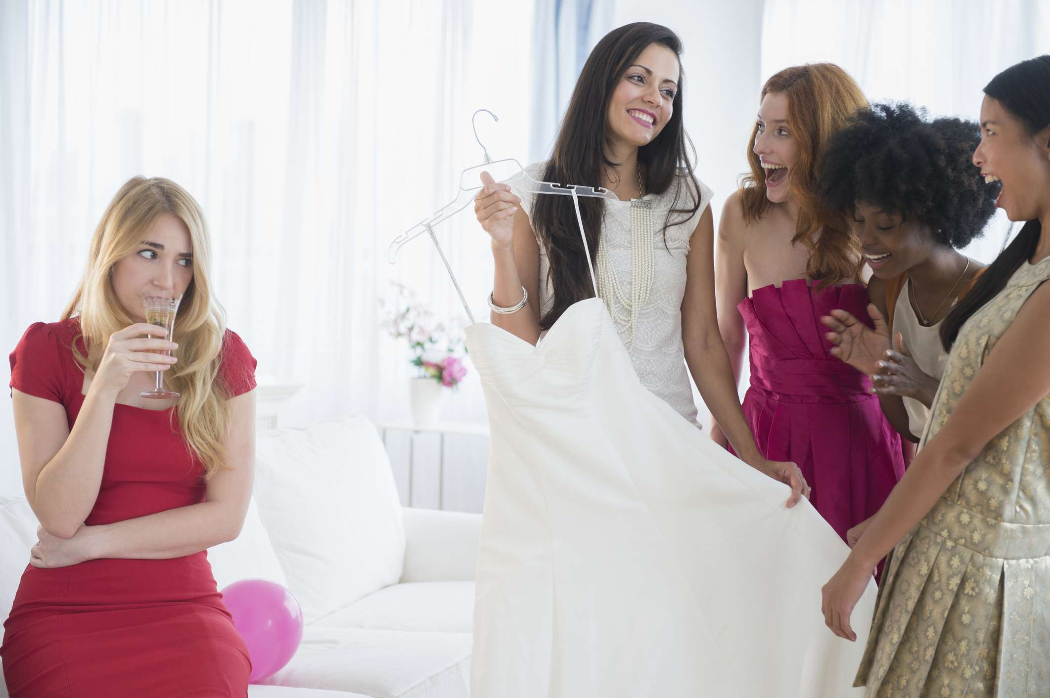 Bride and bride's maids looking at wedding dress while one bride's maid sit aside looking on