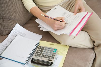 Woman with a calculator and notepad filling out bills on the couch