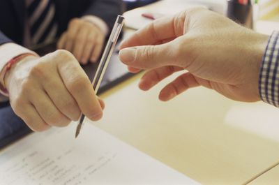 A banker hands a pen across a desk to a person applying for a personal loan.