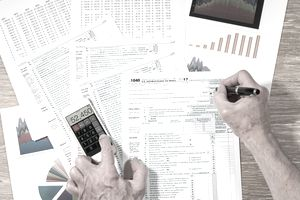 person filling out tax forms with graphs in background and using a smartphone calculator