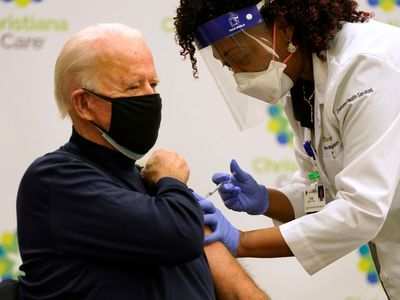president biden getting a covid-19 vaccination from a doctor