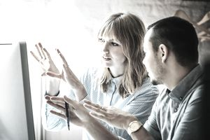 Two people talking in front of a computer making hand gestures.