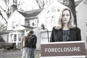 Somber woman holds foreclsure sign in front of a house and sad couple.