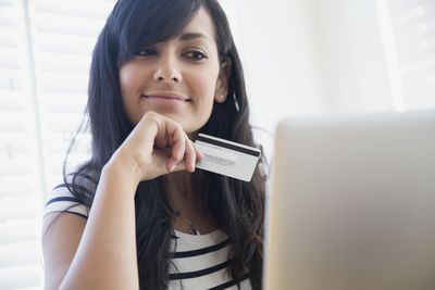 A women with a credit card looking at a computer