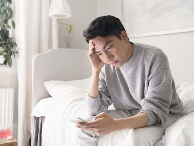 distressed man sitting on bed looking at phone