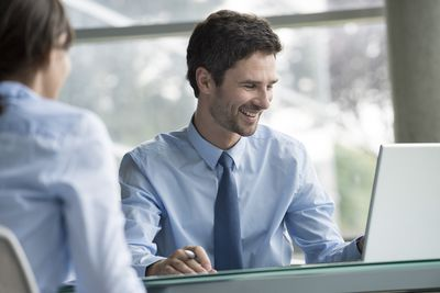 Seated young businessman at laptop helping woman client