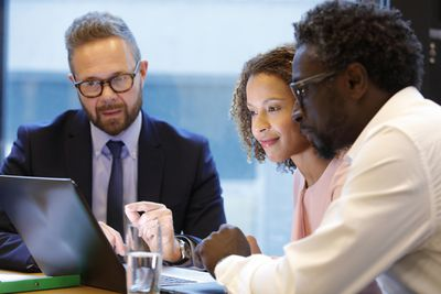 A couple looks over data on a laptop screen while a lender or financial advisor explains.