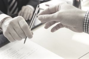 A man accepts a ballpoint pen to put his signature onto a personal loan application
