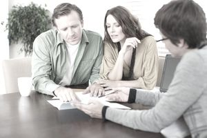 Man and woman meeting with mortgage lender, looking at paperwork