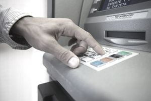 Close-up of person's hand pressing buttons on an ATM