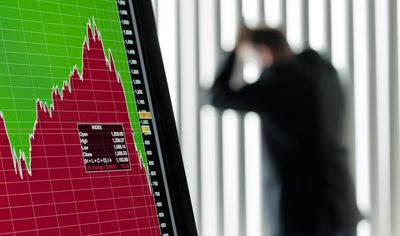 a plummeting stock screen on a computer monitor with a worried margin trader in the background leaning against a window