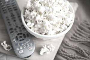 a bowl of popcorn and remote control