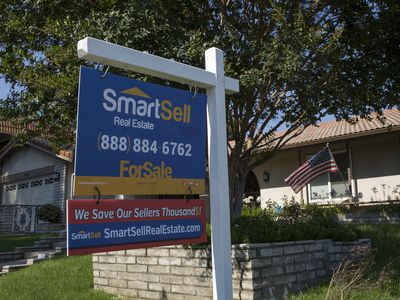 A for-sale sign is seen on a home