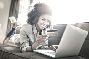 A young woman checking her credit score with a laptop.