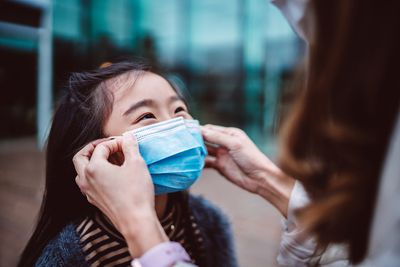 Mom helping her daughter to wear medical face mask